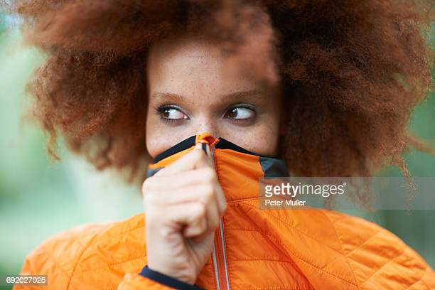 Portrait of woman covering mouth with coat looking away