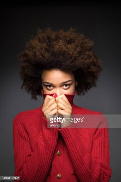 Portrait de femme qui couvre la bouche avec chandail rouge