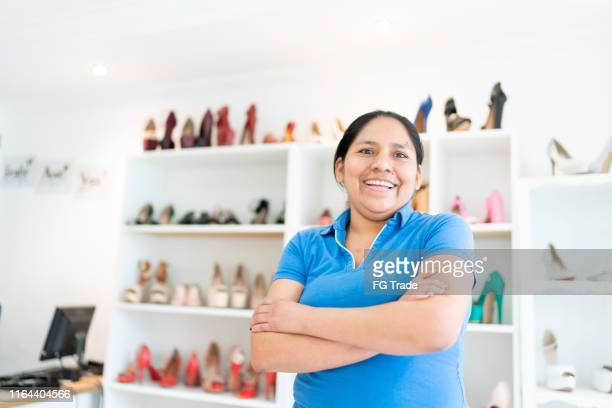portrait of woman crossing arms and looking at camera at shoe store - povo boliviano imagens e fotografias de stock