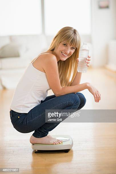 Portrait of woman crouching on weight scales