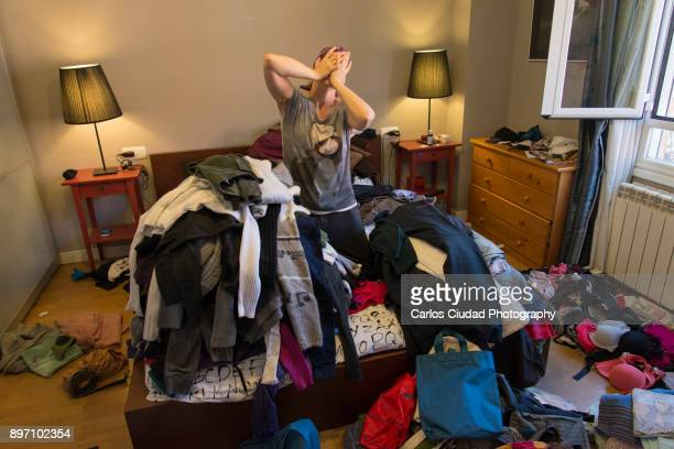 Portrait of woman crying among tiles of clothes in a messy bedroom
