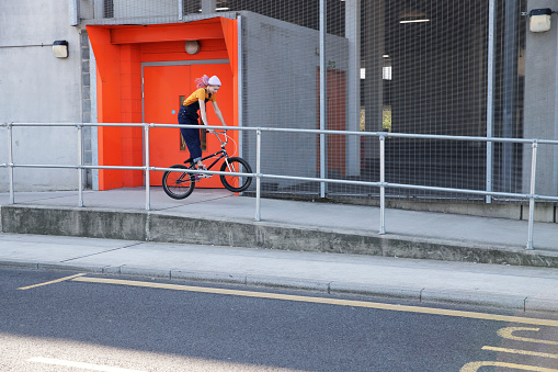 Portrait of woman cycling down ramp outside industrial building - gettyimageskorea