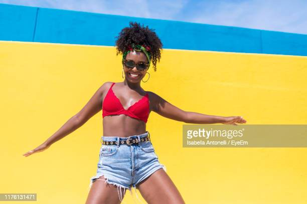 portrait of woman dancing against yellow wall - black shorts stock pictures, royalty-free photos & images