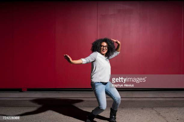 Portrait of woman dancing in front of red wall