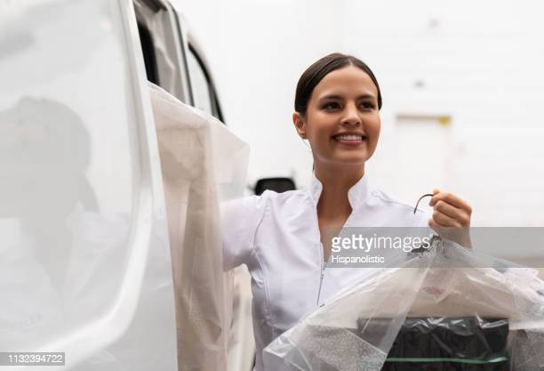 portrait of woman delivering dry cleaned clothes in a van looking away smiling - dry cleaned stock pictures, royalty-free photos & images