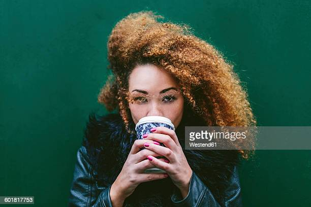 portrait of woman drinking coffee to go in front of a green wall - hair colour stock pictures, royalty-free photos & images