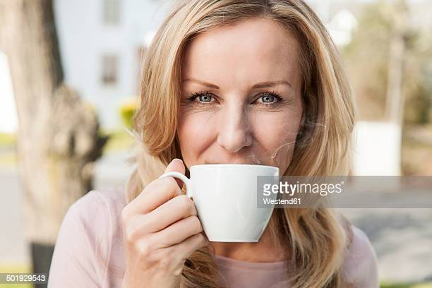 Portrait of woman drinking cup of coffee, close-up