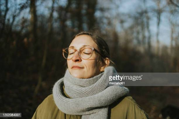 portrait of woman during sunbath in winter - scarf stock pictures, royalty-free photos & images