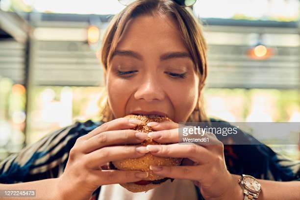 portrait of woman eating a burger - junge frau allein stock-fotos und bilder