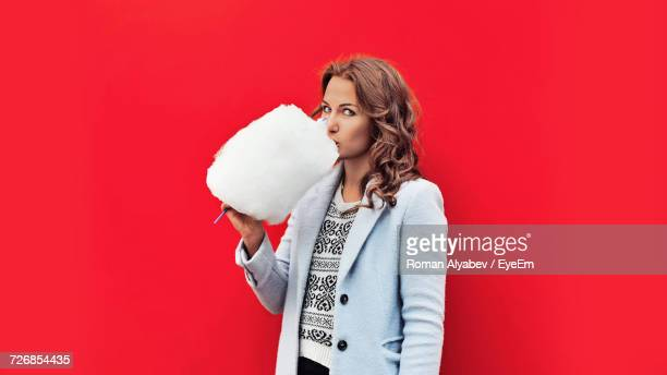 Portrait Of Woman Eating Cotton Candy While Standing Against Red Background