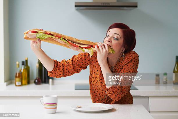 portrait of woman eating giant baguette - excesso imagens e fotografias de stock