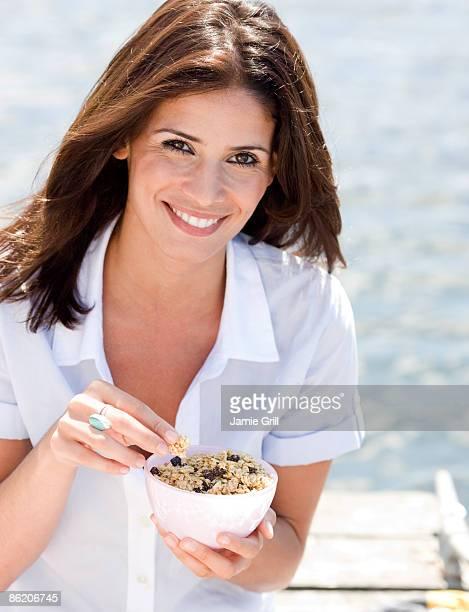 Portrait of woman eating granola on dock