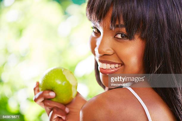 Portrait of woman eating green apple