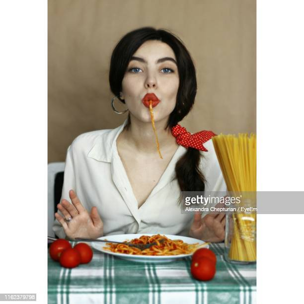 portrait of woman eating pasta while sitting at table - spaghetti stock pictures, royalty-free photos & images