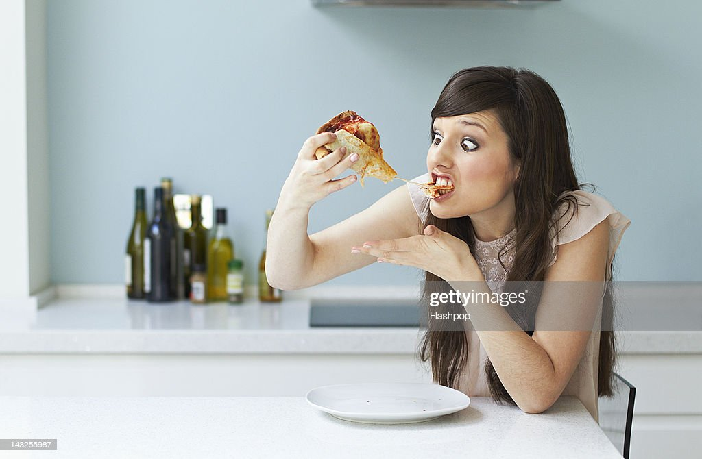 Portrait of woman eating pizza : Stock Photo