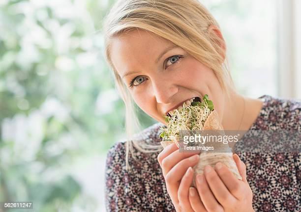 Portrait of woman eating sandwich