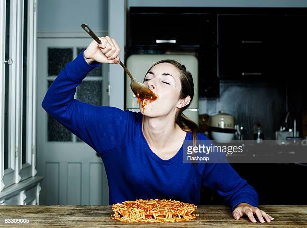 portrait of woman eating spaghetti - abbuffata foto e immagini stock