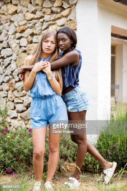 Portrait of woman embracing female friend while standing against wall