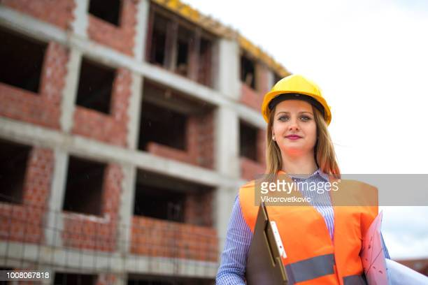 portrait of woman engineer at construction site - saleswoman stock photos and pictures