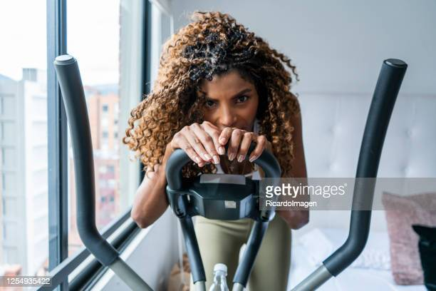 portrait of woman exercising at home through covid-19 quarantine - musculoso stock pictures, royalty-free photos & images