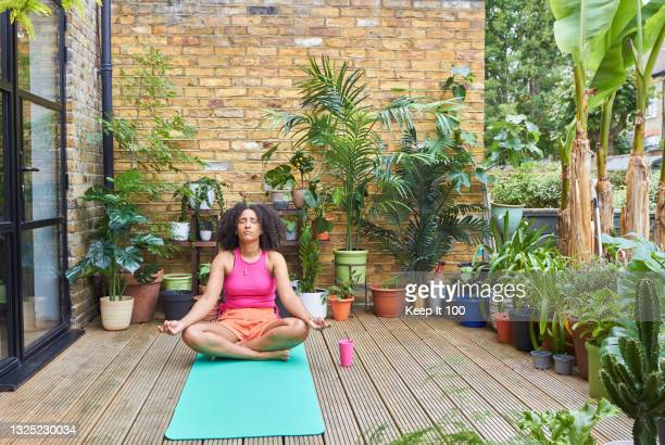 portrait of woman exercising outside at home - one mid adult woman only stock pictures, royalty-free photos & images