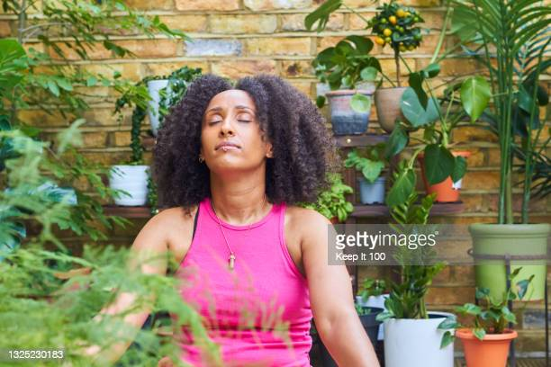 portrait of woman exercising outside at home - buddhism stock pictures, royalty-free photos & images