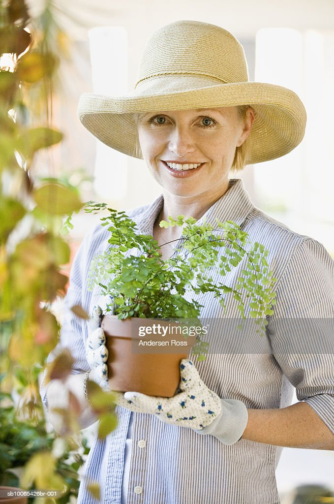 Portrait of woman gardening in conservatory : Foto stock
