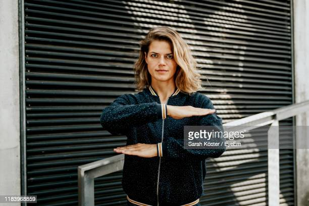 portrait of woman gesturing equal sign while standing against closed shutter - gleichheit stock-fotos und bilder
