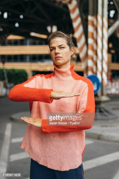 portrait of woman gesturing equal sign while standing on road - gleichheit stock-fotos und bilder