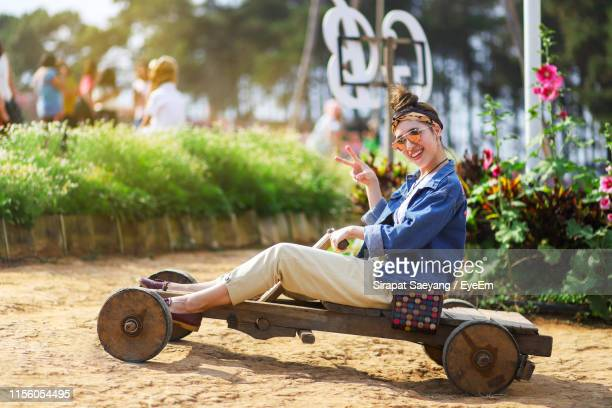 portrait of woman gesturing peace sign while sitting on cart in park - 25 29 anos imagens e fotografias de stock