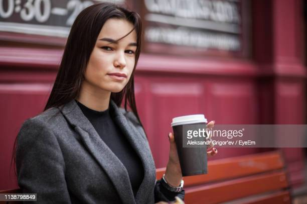 Portrait Of Woman Having Coffee Against Wall