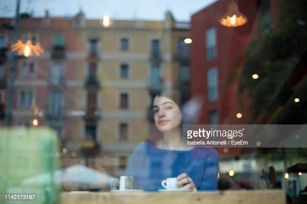 portrait of woman having coffee in cafe seen through glass window - photographed through window stock pictures, royalty-free photos & images