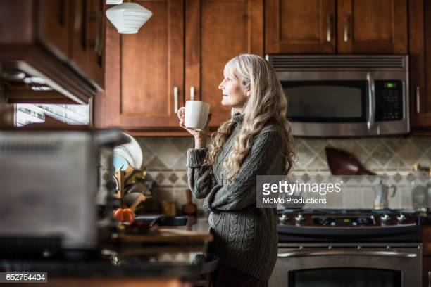 Portrait of woman (60yrs) having coffee in kitchen