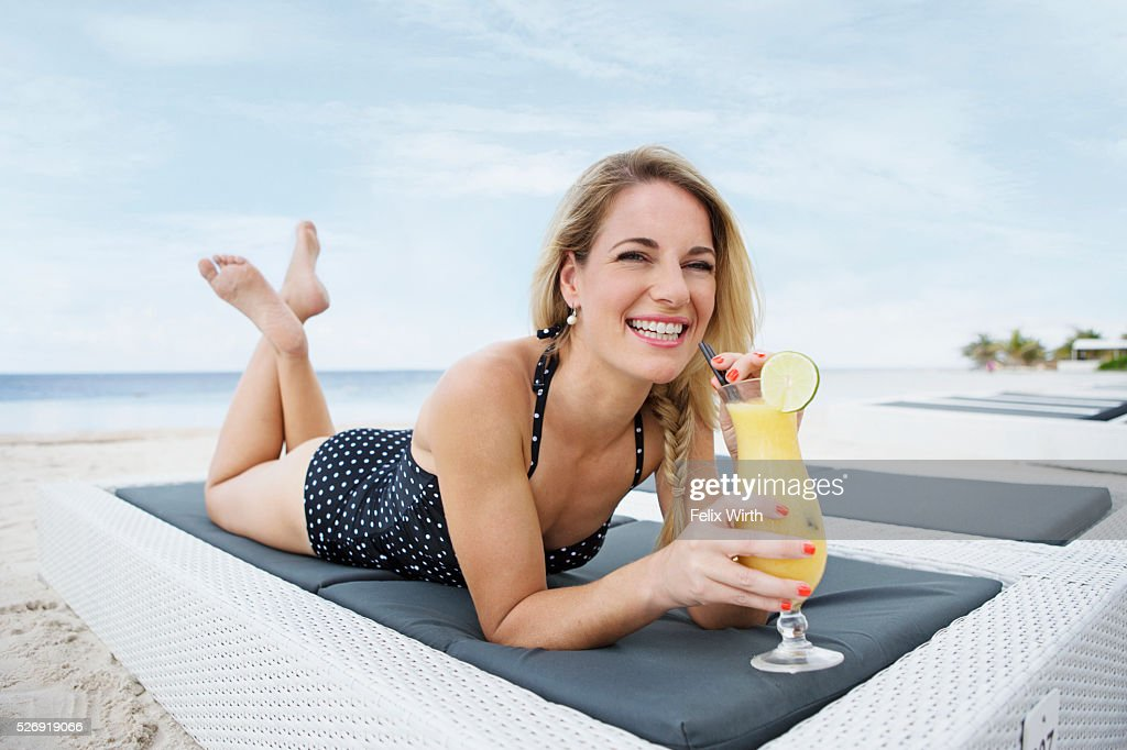 Portrait of woman having drink on deck chair on beach : Photo