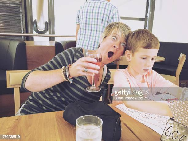Portrait Of Woman Having Drink While Making Face With Son At Restaurant