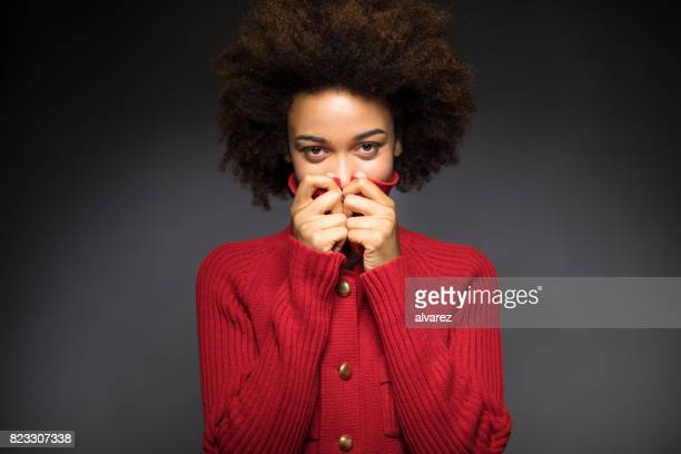 portrait of woman hiding face with red sweater - obscured face stock pictures, royalty-free photos & images