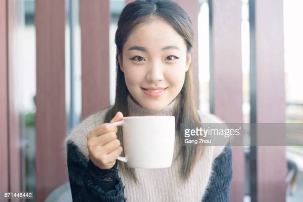 portrait of woman holding a cup of coffee at balcony - woman cradling mug stock pictures, royalty-free photos & images