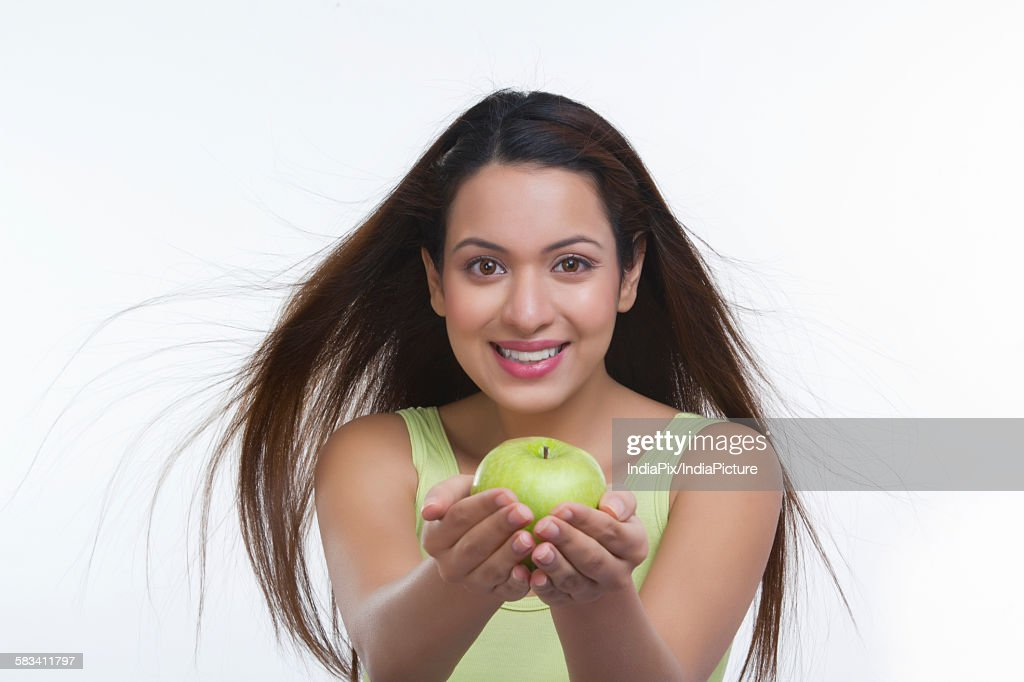 Portrait of woman holding an apple : Stock Photo