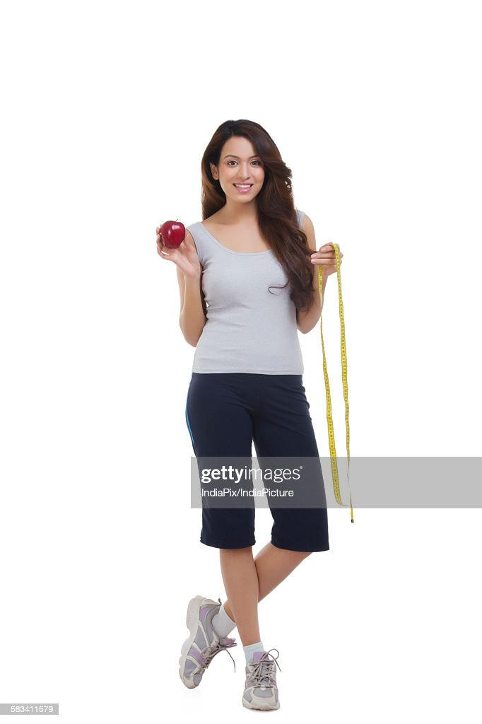 Portrait of woman holding apple and measuring tape : Stock Photo