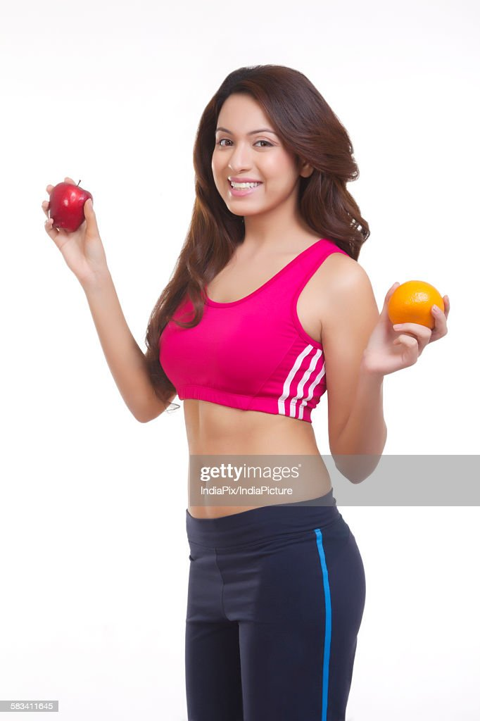 Portrait of woman holding apple and orange : Stock Photo