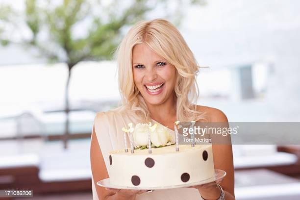 Portrait of woman holding birthday cake