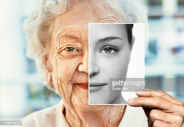 portrait of woman holding black and white younger photo of herself - aging process stock pictures, royalty-free photos & images