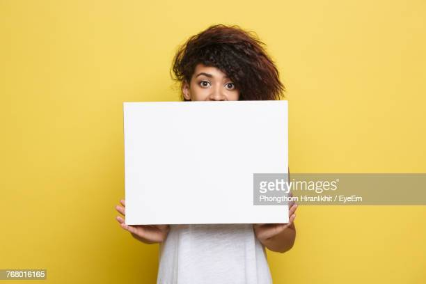 portrait of woman holding blank paper against yellow background - cogiendo fotografías e imágenes de stock