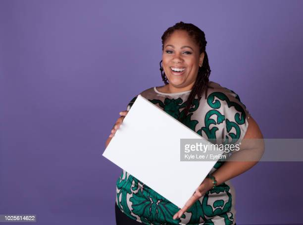 portrait of woman holding blank placard while standing against purple background - person holding up sign stock pictures, royalty-free photos & images