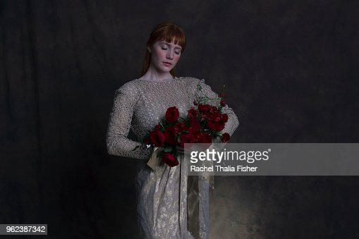 Portrait of woman holding bouquet of roses as if in a classic oil painting