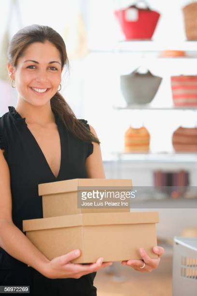 Portrait of woman holding boxes in retail store