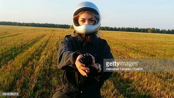 Portrait Of Woman Holding Camera And Standing On Grassy Field Against Sky