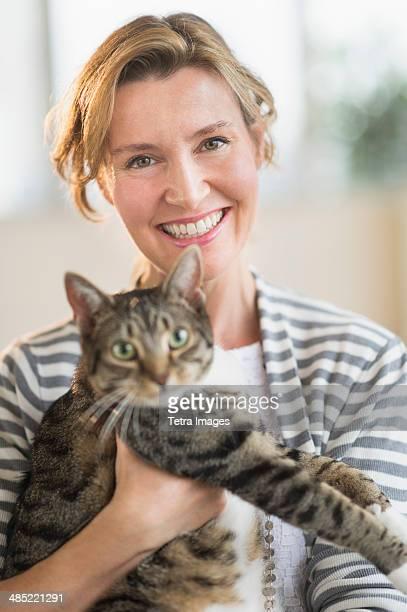 Portrait of woman holding cat