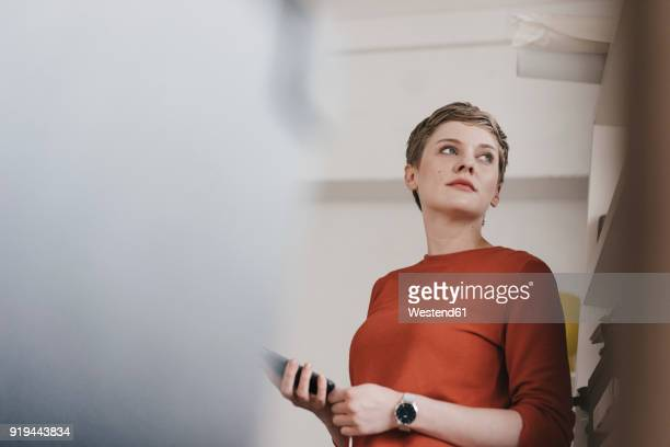 portrait of woman holding cell phone - one mid adult woman only stock pictures, royalty-free photos & images