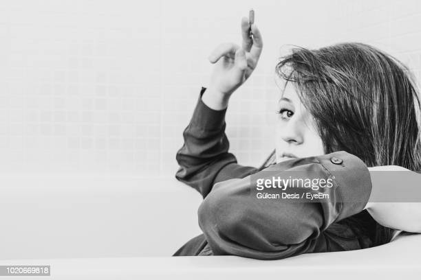 portrait of woman holding cigarette in bathtub at home - one young woman only stock pictures, royalty-free photos & images